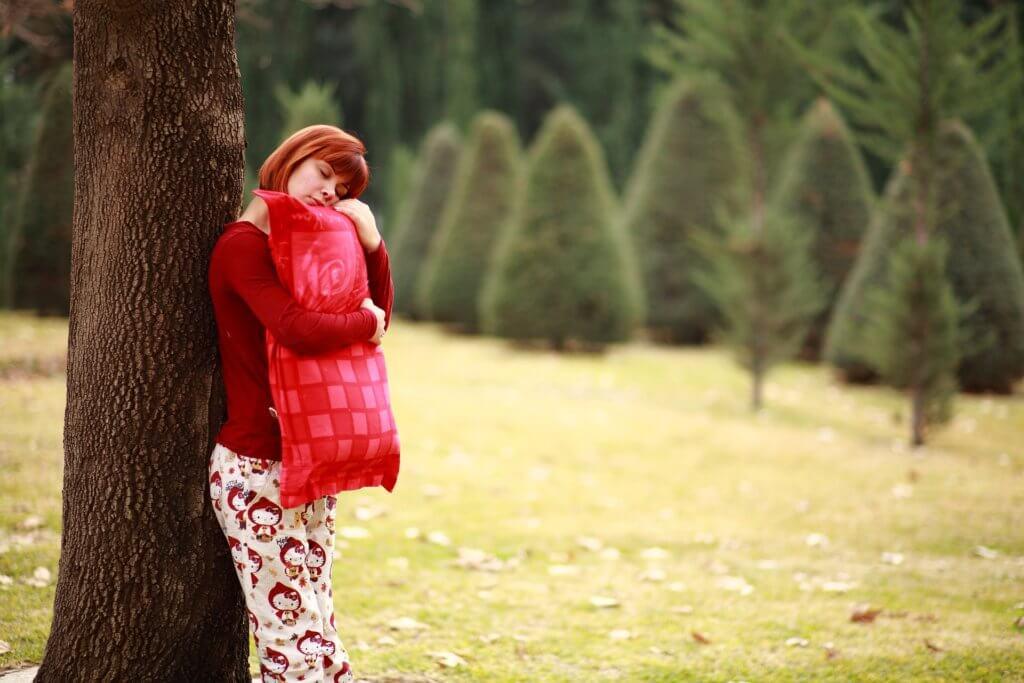 vrouw stat tegen boom met kussen